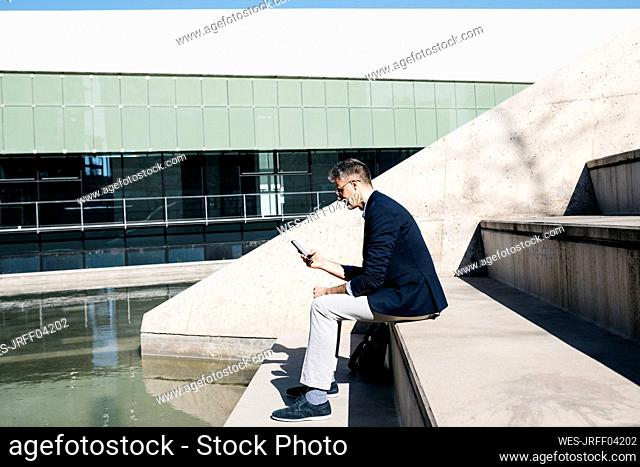 Gray-haired businessman sitting on stairs at a pool using cell phone