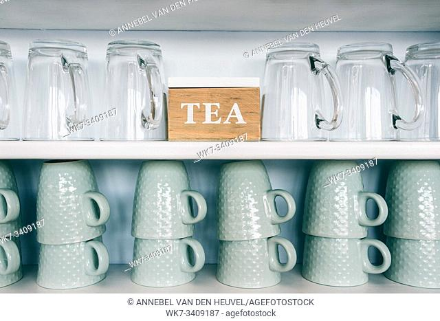 tea cups and coffee mugs on a kitchen shelf with a tea box Rack focus. Close up. wooden shelf