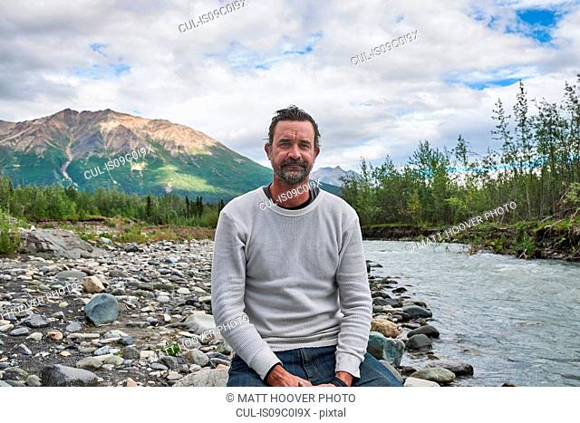 Man relaxing by stream, scenic view in background, Chitina, Alaska, United States