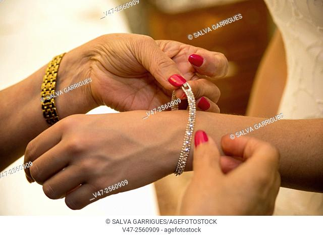 A woman puts a bracelet to the bride's wedding day