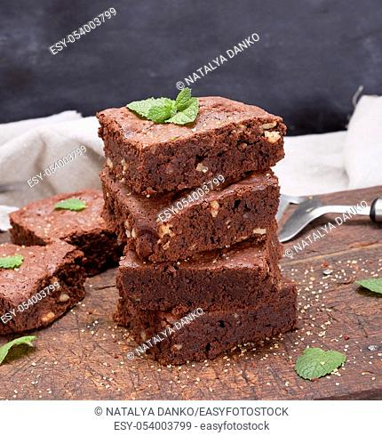 stack of baked square pieces of chocolate brownie pie with walnuts, close up