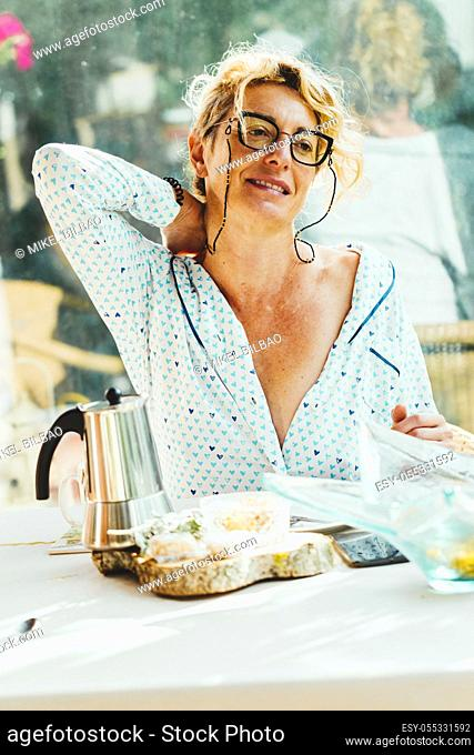 Blonde young mature woman with glasses in pyjamas at home in breakfast time, with backache