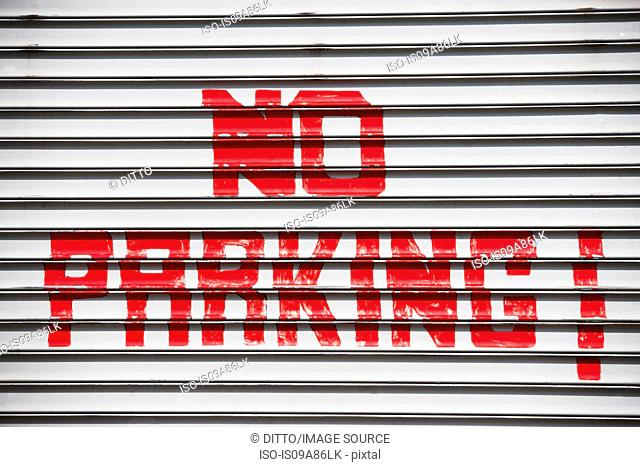 Red hand painted no parking sign