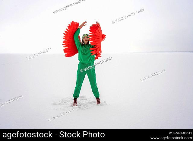 Woman in green bird costume looking up while standing against sky