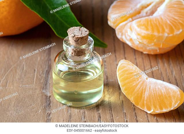 A bottle of essential oil with fresh tangerines