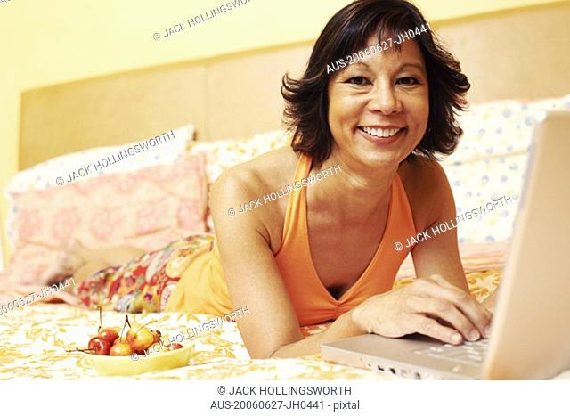 Portrait of a mature woman smiling and using a laptop