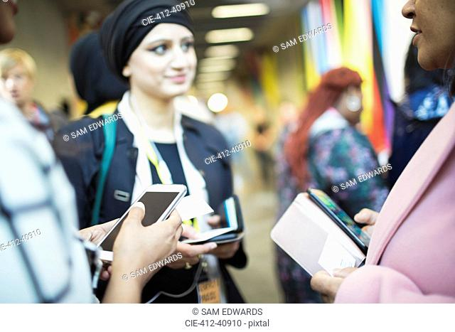 Businesswomen with smart phones, networking at conference