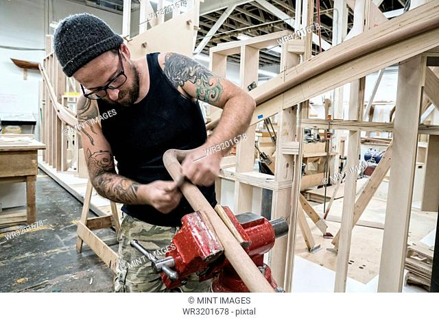 Caucasian carpenter working on a spiral staircase railing in a large woodworking shop