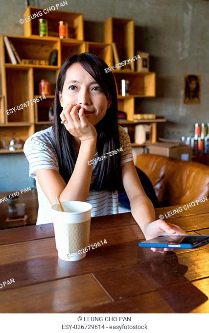 Woman thinking about something in coffee shop