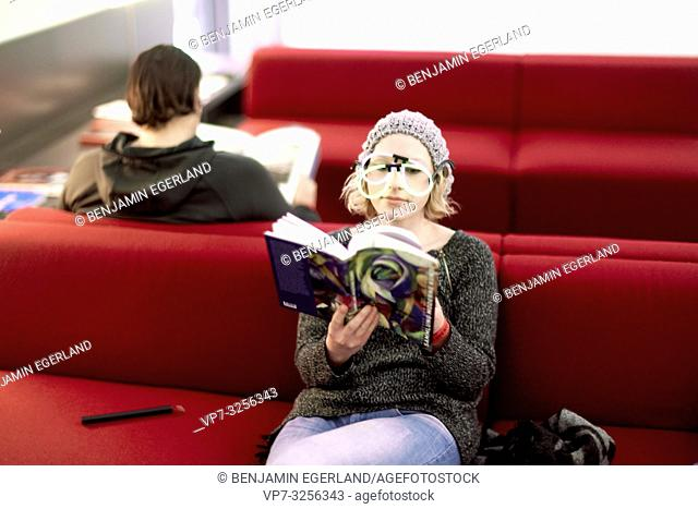 artist woman reading books while sitting on red couch in public, studying, in Zmunich, Germany