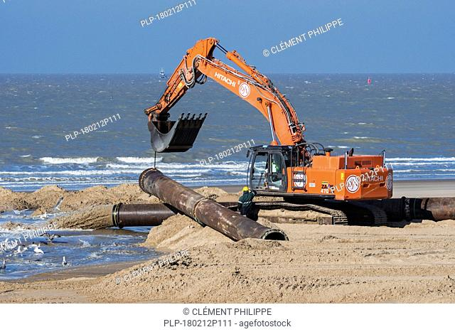 Hydraulic excavator installing pipeline during sand replenishment / beach nourishment works along the Belgian coast at Ostend, Belgium