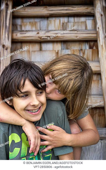 Young female child enjoys kissing her happy boyfriend