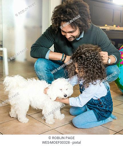 Father and daughter playing with a little dog at home