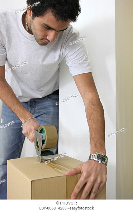 young man wrapping cardboard