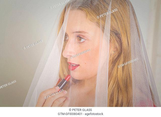 Teenage girl applying lipstick