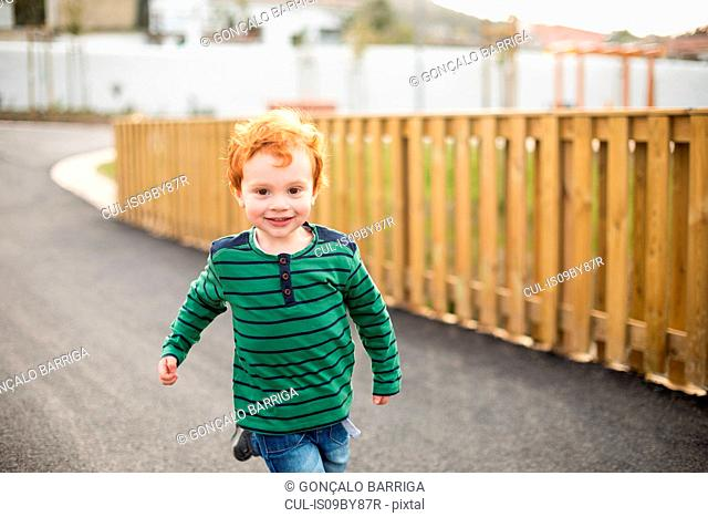 Boy running on road in residential area