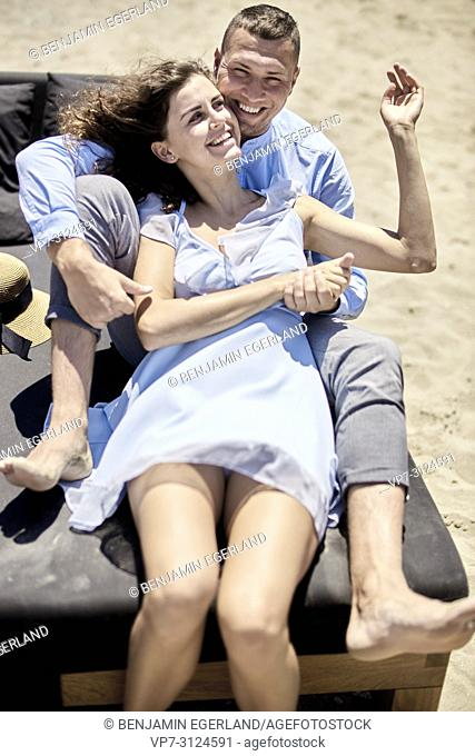 couple sitting on sunbeds at beach, vacations, summer, love, playful, togetherness, happiness, candid, unposed
