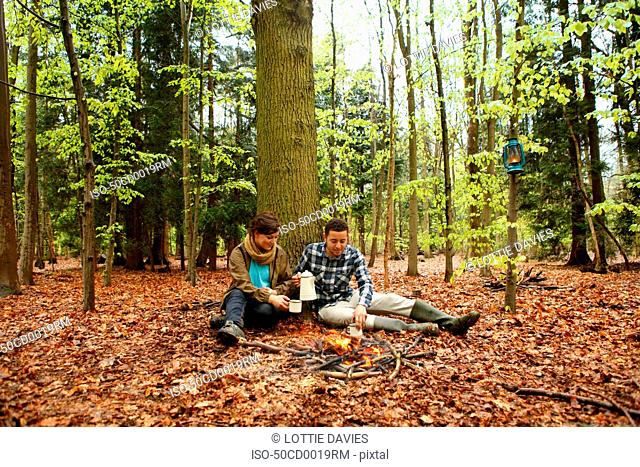 Couple drinking coffee by campfire