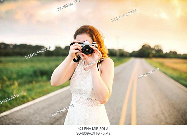 Woman on rural road taking photograph using camera
