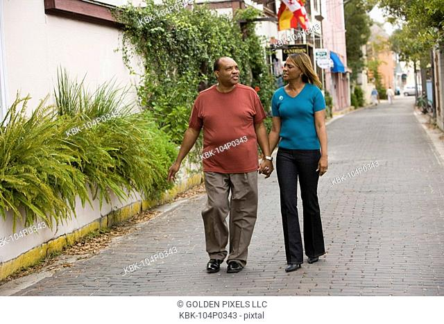 Mature African American couple strolling down street