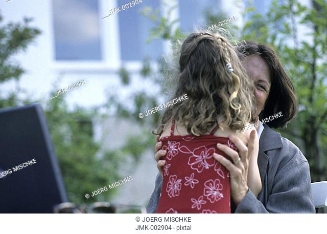 A woman, businesswoman, mother, 40-45 45-50 years old, and a little girl, young, 1-5 5-10 years old, in the summerly garden