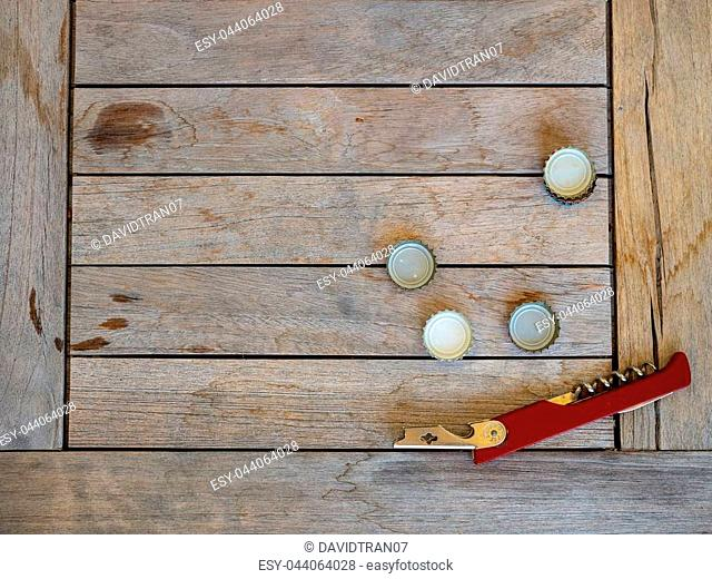 Some beer bottle caps and bottle opener sitting on wooden table outdoors at party event
