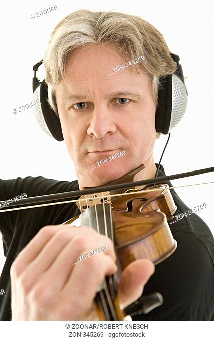Mann spielt Violine mit Kopfhörern auf dem Kopf