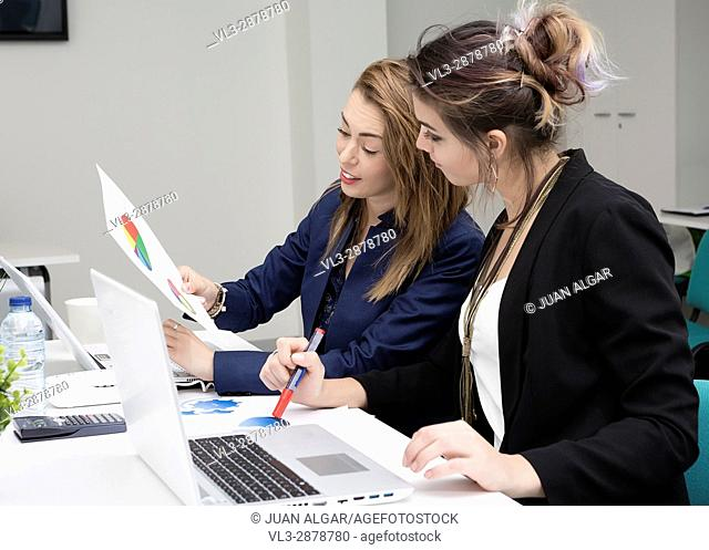 Cheerful businesswomen looking at the diagram working in the office sitting at the laptop