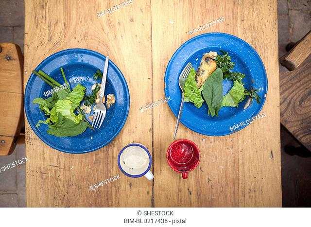 High angle view of plates of greens on table
