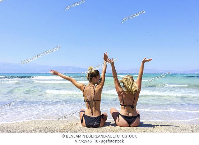 best friends, two girls sitting in bikini on beach. Dutch ethnicity. At holiday destination Chrissi Island, Crete, Greece