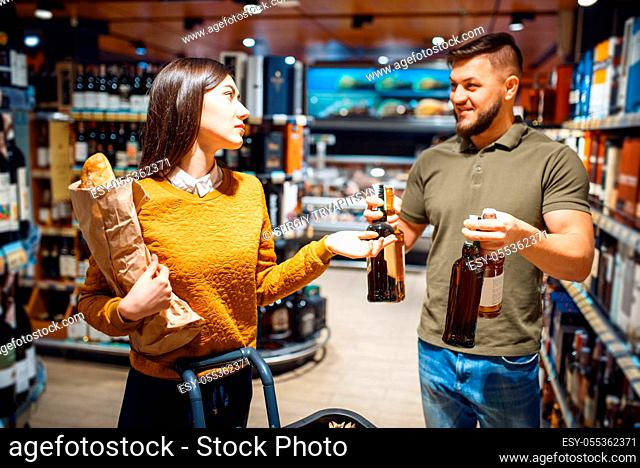 Attractive couple choosing alcohol in grocery supermarket. Man and woman with cart buying beverages in market, customers shopping food and drinks