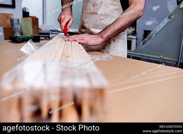 Male frame maker cutting plastic on wooden plank while working in store