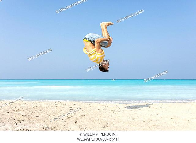 Young man doing a somersault on the beach