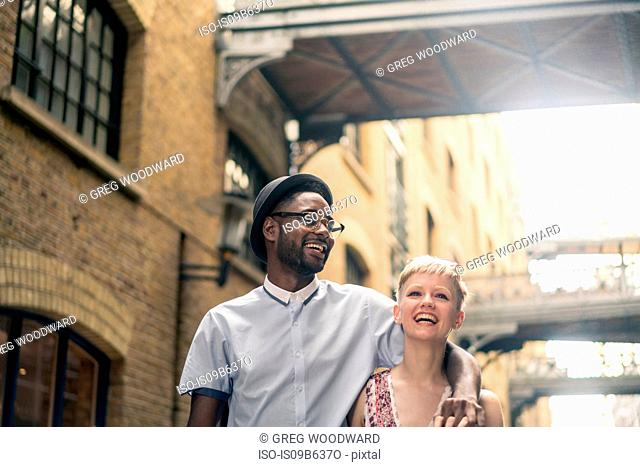 Young couple walking outdoors, smiling