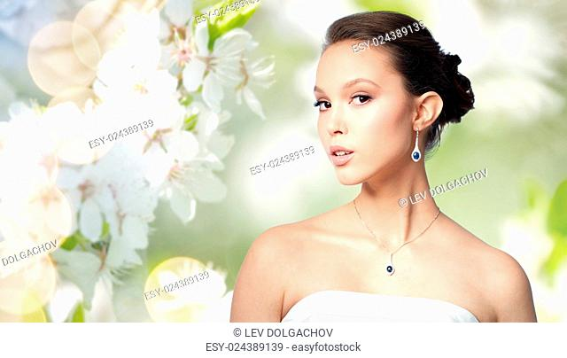 beauty, jewelry, wedding accessories, people and luxury concept - beautiful asian woman or bride with earring and pendant over natural spring cherry blossom...