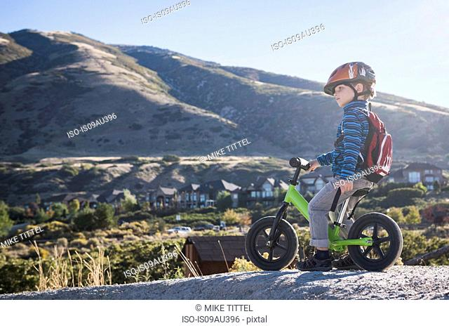Boy sitting on balance bike in front of mountain, Draper cycle park, Missoula, Montana, USA