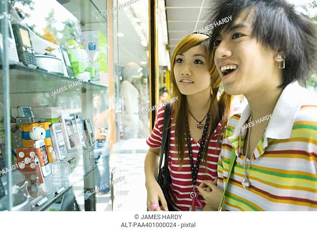 Teenage couple looking at shop window