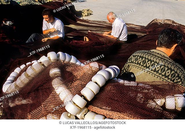 Fishermen sew the nets, in fishing port of Adra. Almeria province, Andalucia, Spain