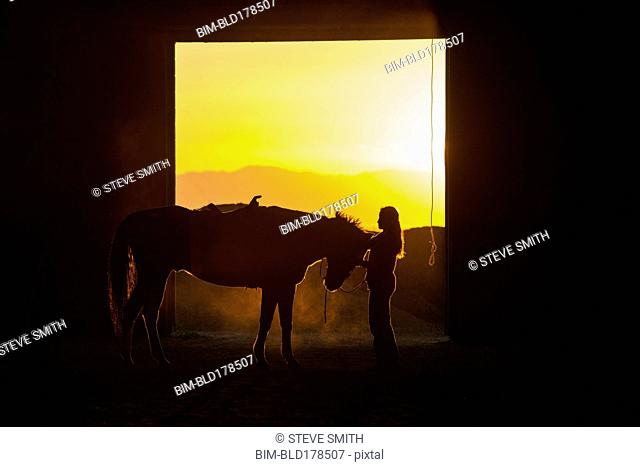 Caucasian woman grooming horse in barn