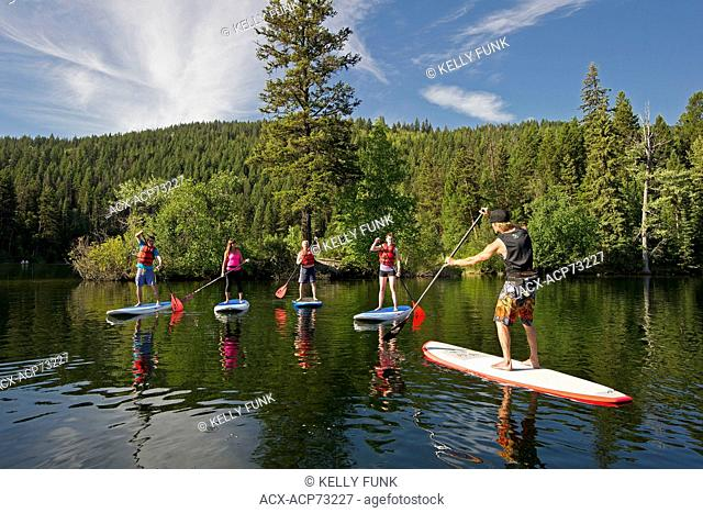 A group of paddle boarders get instructed by a professional on Heffley Lake, North of Kamloops in the Thompson Okanagan region of British Columbia, Canada