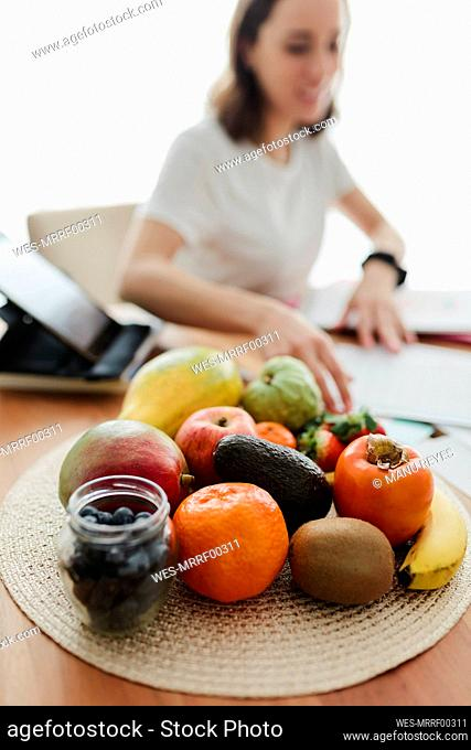 Fruit kept on table with woman working in background at home