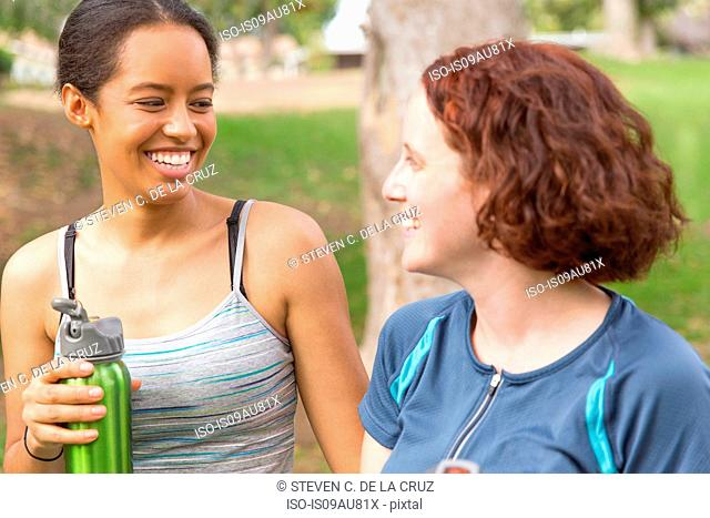Head and shoulders of young women carrying water bottles face to face smiling