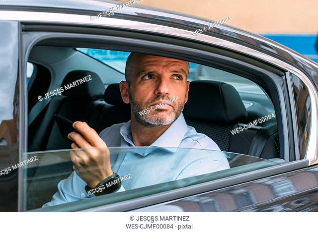 Businessman sitting on a backseat of a car using smartphone and looking around