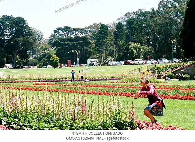 A female tourist bends down to take a cellphone photograph of flowers in a formal garden in front of the Conservatory of Flowers