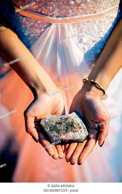 Bride holding quartz crystal, mid section