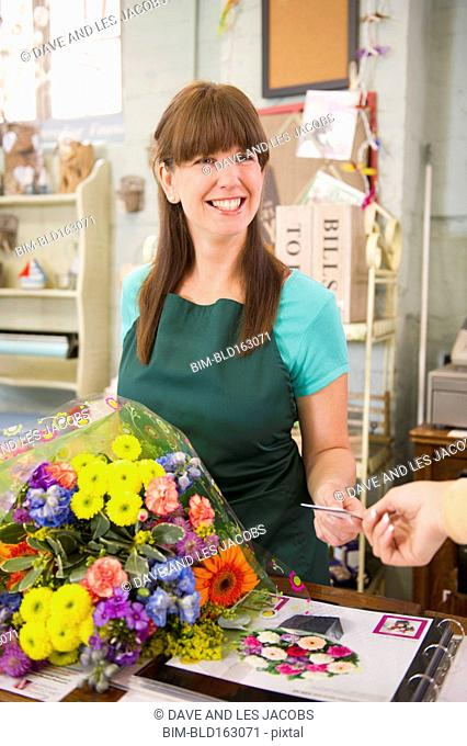 Employee taking payment from customer in florist shop