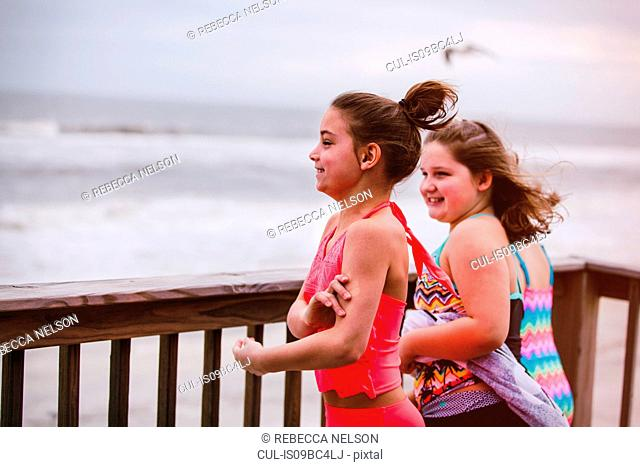 Three girls looking out at sea from balcony, Dauphin Island, Alabama, USA
