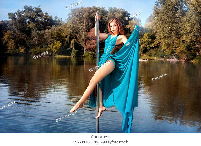 Girl in dress dancing on a pole in the lake. See more photos of this series