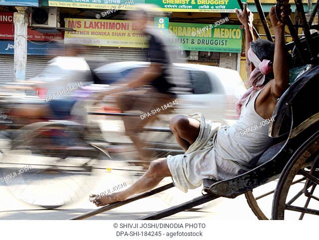 hand rickshaw puller is taking rest on roadside at Kolkata India