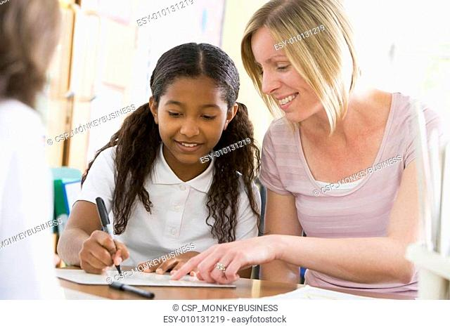 A schoolgirl sitting with her teacher in class